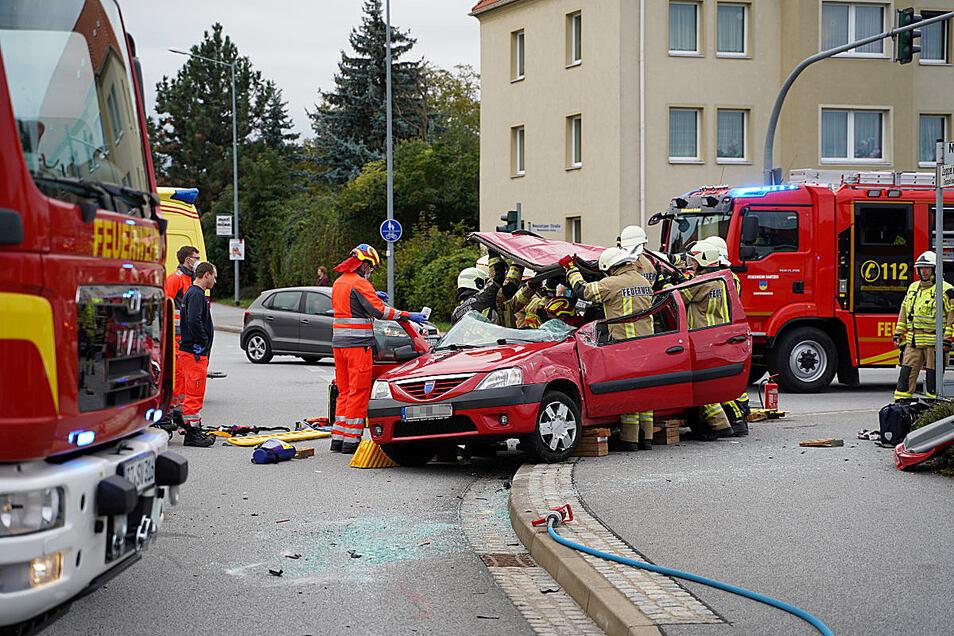 Unfall in Bautzen am späten Freitagnachmittag auf der Kreuzung Neusalzaer/Zeppelinstraße: Feuerwehrleute schneiden das Dach eines Dacia ab, um den eingeklemmten Fahrer zu befreien.