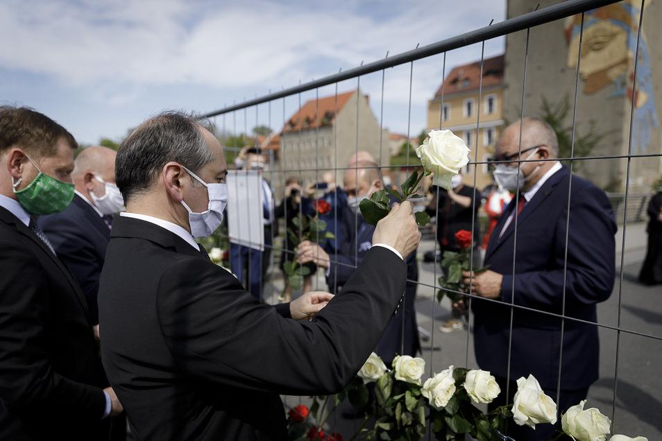 Der Görlitzer Oberbürgermeister Octavian Ursu (vorn) steckt eine Rose des Gedenkens in den Zaun auf der Altstadtbrücke.
