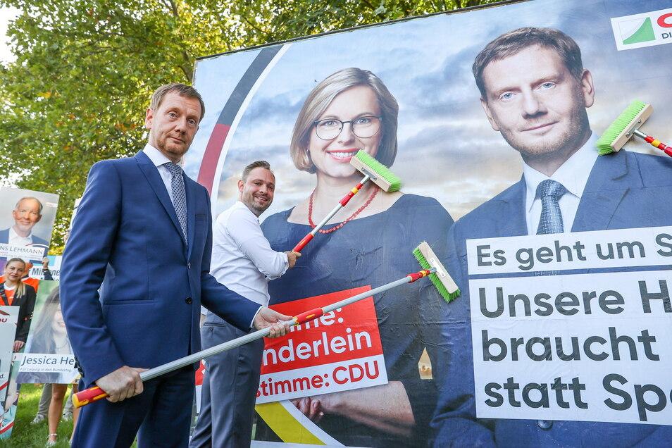 Michael Kretschmer klebt mit Sachsens CDU-Generalsekretär Alexander Dierks ein Wahlplakat für die Bundestagswahl.