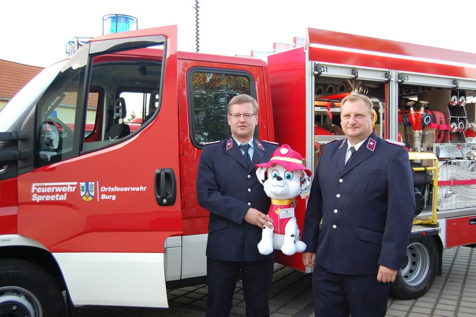 Der Burger Ortswehrleiter Daniel Nowotnick (links), Spreetals Gemeindewehrleiter Oliver Puls und das neue Maskottchen vor dem Tragkraftspritzenfahrzeug.