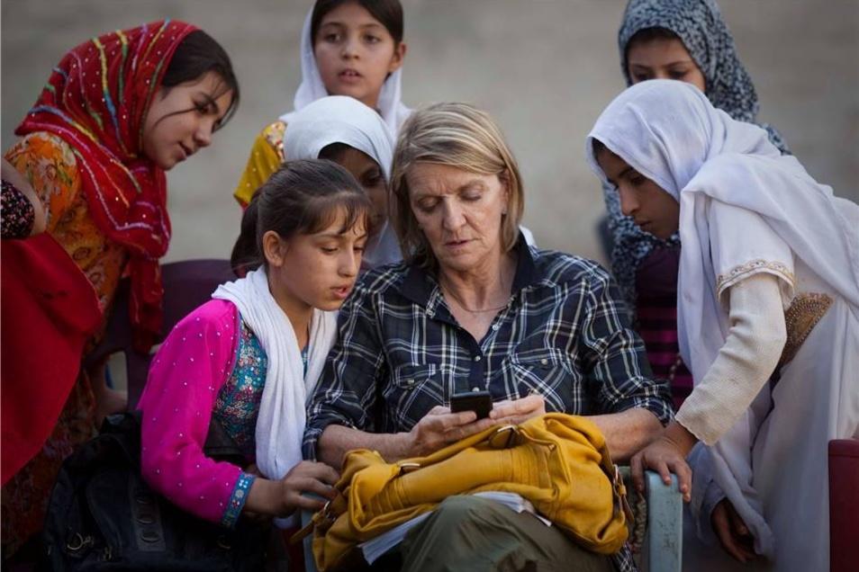 Dieses Bild vom Oktober 2011 zeigt Kathy Gannon, die Kollegin von Anja Niedringhaus, die bei dem Angriff auf das Auto der Journalistinnen schwer verletzt wurde.Hier zeigt die Kanadierin Schülerinnen in Kandahar ihr Telefon.