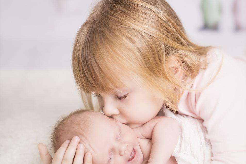 Ein Küsschen für das Geschwisterchen: So wünschen es sich Eltern, wenn die Familie größer wird. Doch auch das große Kind hat Bedürfnisse und muss sich an die neue Situation erst gewöhnen.