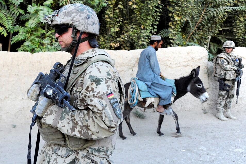 Deutsche Soldaten bei einem Patrouillengang durch die afghanische Ortschaft Nawabad nahe Kundus. Nach dem Abzug der Bundeswehr hat die Debatte um künftige Auslandsmissionen bereits begonnen. Foto: dpa/Maurizio Gambarini