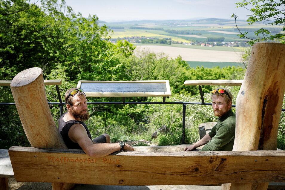 Christoph Kretzschmar (links) und Philipp Weise von der Firma Holzgestalten aus Ostritz sitzen vor der neuen Panorama-Tafel am Aussichtspunkt Pfaffendorfer Blick auf der Landeskrone. Sie wurde voriges Jahr im Mai errichtet.
