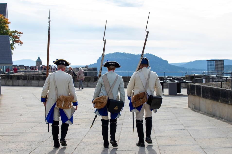 Drei als Soldaten der Sächsischen Infanterie in den Tuchfarben Weiß-Blau verkleidete Menschen während der Patrouille auf der Festung Königstein.