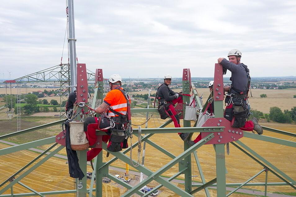 Die Monteure warten auf das nächste Bauteil, das im Hintergrund bereits an Kranseilen heranschwebt. Dieses Foto wurde von einer Drohne aufgenommen, mit der der Konzern die Arbeiten am neuen Masten bei Zeithain dokumentiert.