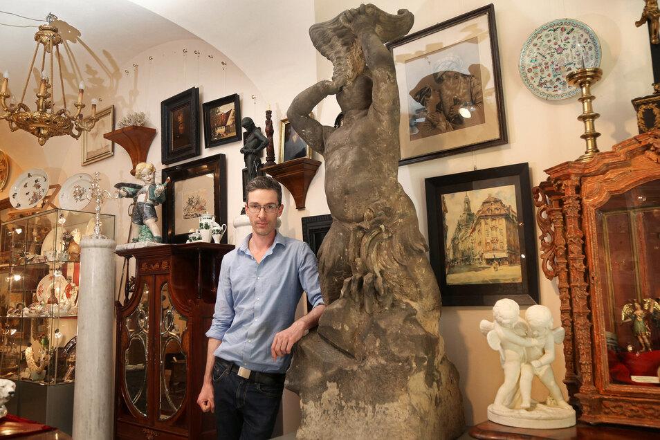 Ein Original einer Tiefenauer Brunnenfigur steht im Dresdner Kunsthandel am Schloss, wo Mitarbeiter Felix Pietschmann sich entspannt dagegen lehnen kann. Dass die tonnenschwere Figur umkippt, ist eher unwahrscheinlich.