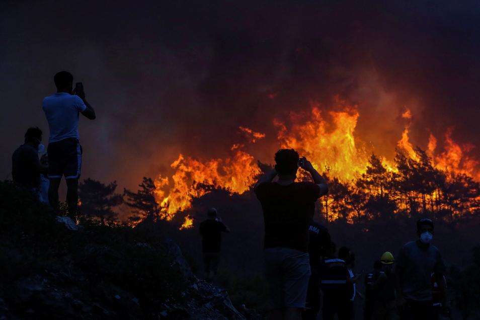 Türkei, Milas: Anwohner beobachten einen Waldbrand in der Nähe des Dorfes Akcayaka. In der Türkei sind weiterhin große Brände außer Kontrolle.