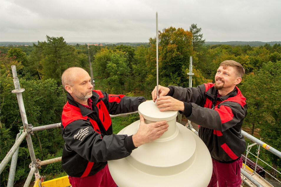 Nachdem die Vase auf dem Dach befestigt ist, bringen Frank Neubert (re.) und Jan Hett den Blitzableiter an.