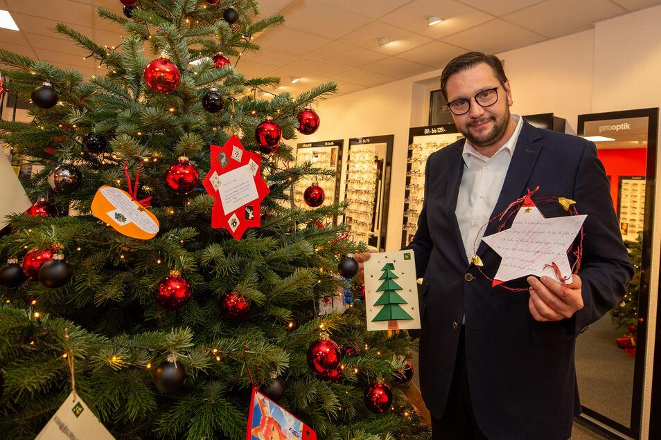 Mathias Lange von Pro Optik zeigt die Kinder-Wunschzettel am Baum in seinem Geschäft.