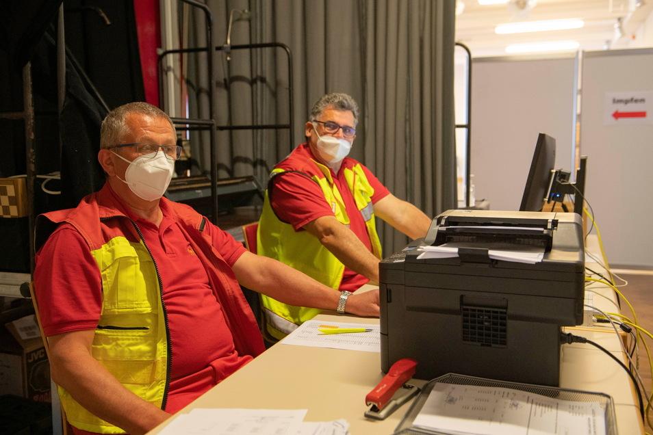 An ihnen kommt niemand vorbei: Wolfgang Dietel und Olaf Stein nehmen die Unterlagen der zu Impfenden entgegen und prüfen, ob alles seine Richtigkeit hat.