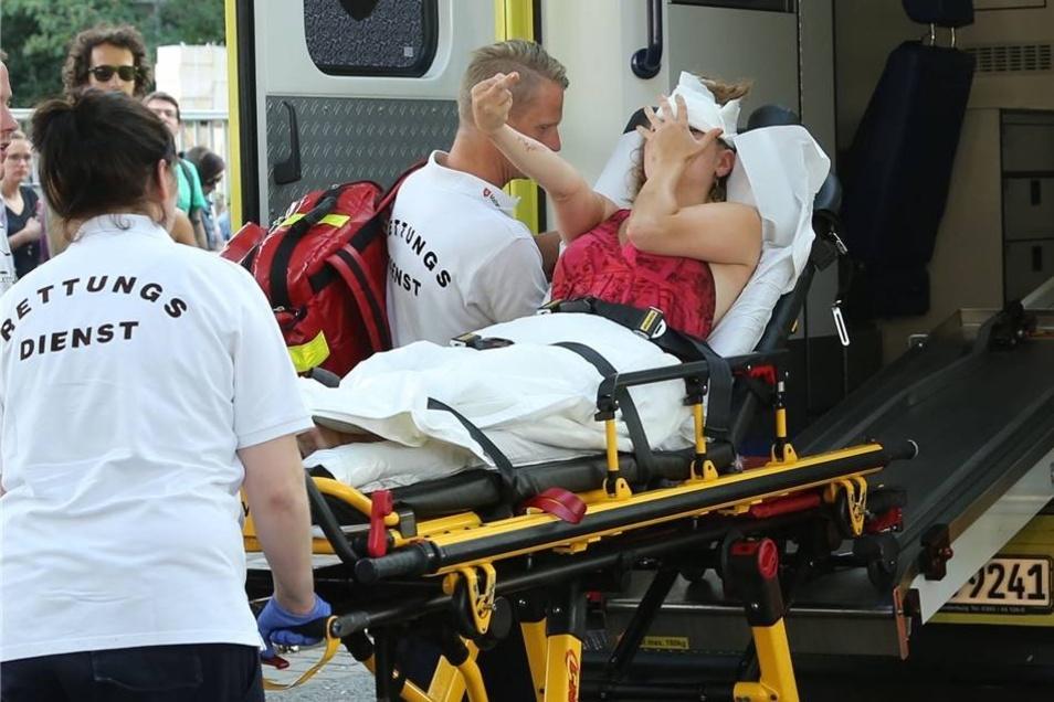 Eine verletzte Gegendemonstrantin wird in einen Rettungswagen geschoben.