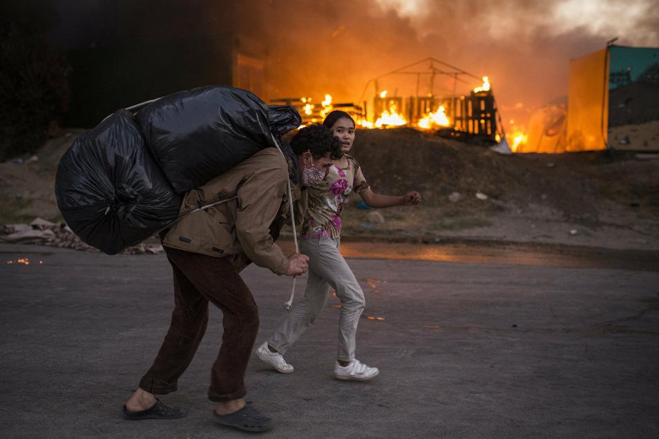 Migranten fliehen vor neu ausgebrochenen Feuern mit ihren Habseligkeiten aus dem Flüchtlingslager Moria, nachdem zuvor bereits mehrere Brände das Lager nahezu vollständig zerstört hatten.