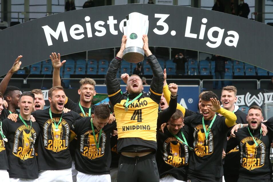 Kapitän Sebastian Mai trägt das Trikot von Tim Knipping, als er nach dem 1:0-Erfolg in Wiesbaden den Pokal für den Drittliga-Meister in die Höhe reckt. So ist der Verteidiger zwar wegen des Trauerfalles in der Familie nicht vor Ort, aber doch dabei.