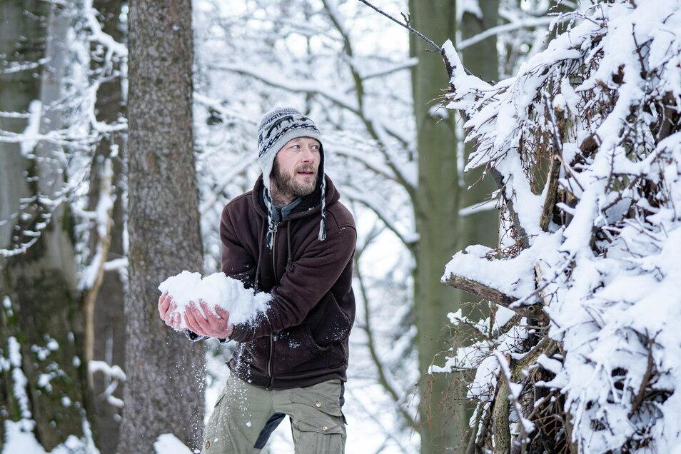 Mit seinen Armen schaufelt Michael Schubert jede Menge Pulverschnee auf seine provisorische Holzhütte...