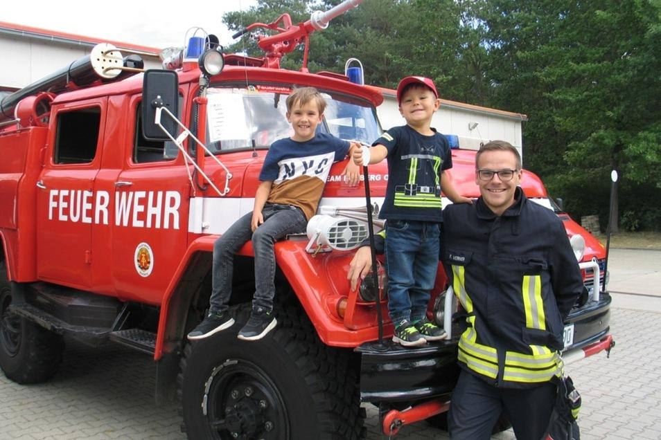 Lennox (9) ist seit einem Jahr mit großem Eifer in der Jugendfeuerwehr Boxberg dabei und der kleine Taylor (4) schon ein großer Fan. Zusammen mit Felix Werner, dem stellvertretenden Ortswehrleiter, freuen sie sich auf das Feuerwehr- und Familienfest.