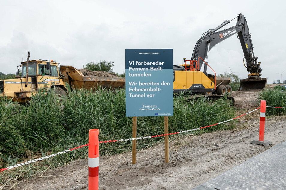 """Dänemark, Rødbyhavn: Baumaschinen heben hinter einem Schild mit der deutsch, dänischen Aufschrift """"Wir bereiten den Fehmarnbelt-Tunnel vor"""" einen Entwässerungsgraben auf dem zukünftigen Baugelände aus."""