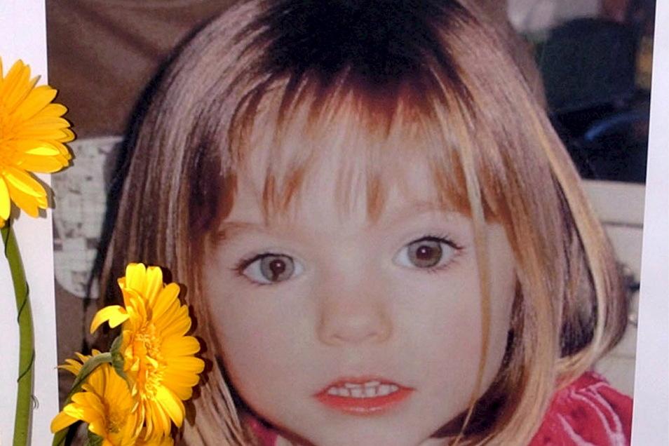 Blumen stehen vor einem Bild, das die verschwundenen Madeleine McCann (Maddie) auf einem Foto zeigt, das ihre Eltern 2007 im Zusammenhang mit dem Verschwinden des Kindes veröffentlich haben.