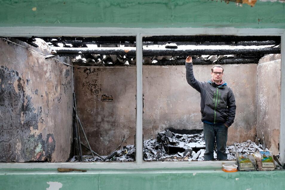 Mike Schneider zeigt auf das Dach der Laube, an dem der Brand ausgebrochen ist. Das Feuer griff auf den Hühnerstall über.