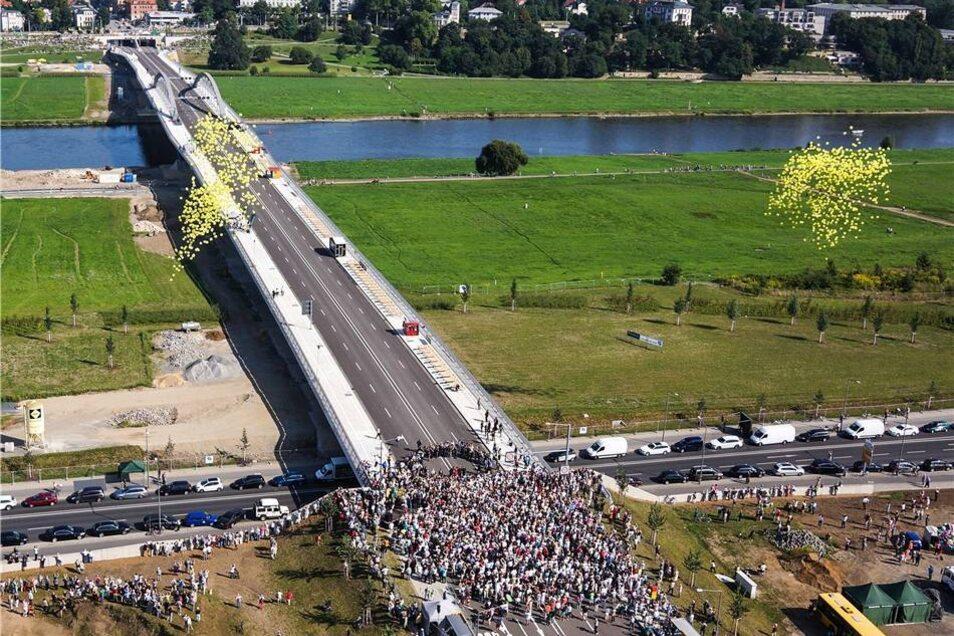 Als das Band durch war, stiegen gelbe Luftballons in den Himmel und der erste Schwung enterte die Brücke.