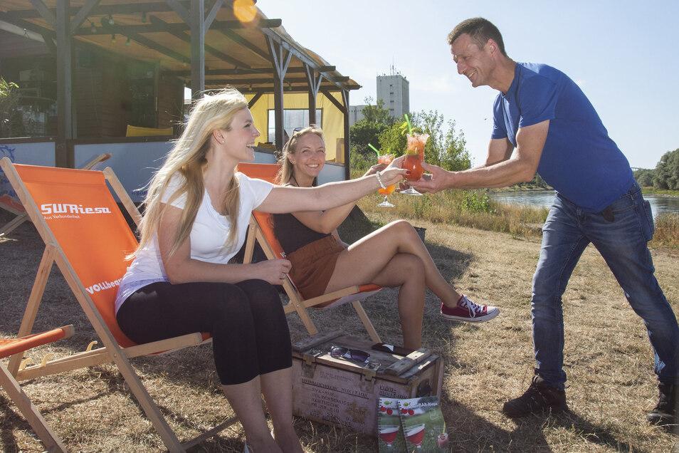 Sommerbar-Betreiber Tilo Löwe serviert leckere Cocktails für Linda (links) und Jenny am Riesaer Elbufer.