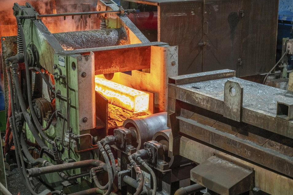 Ein sogenannter Stahlknüppel rollt aus dem Ofen ins Walzwerk. Feralpi schmilzt in Riesa aus Schrott neuen Stahl, der dann weiter zu Baustahl verarbeitet wird.