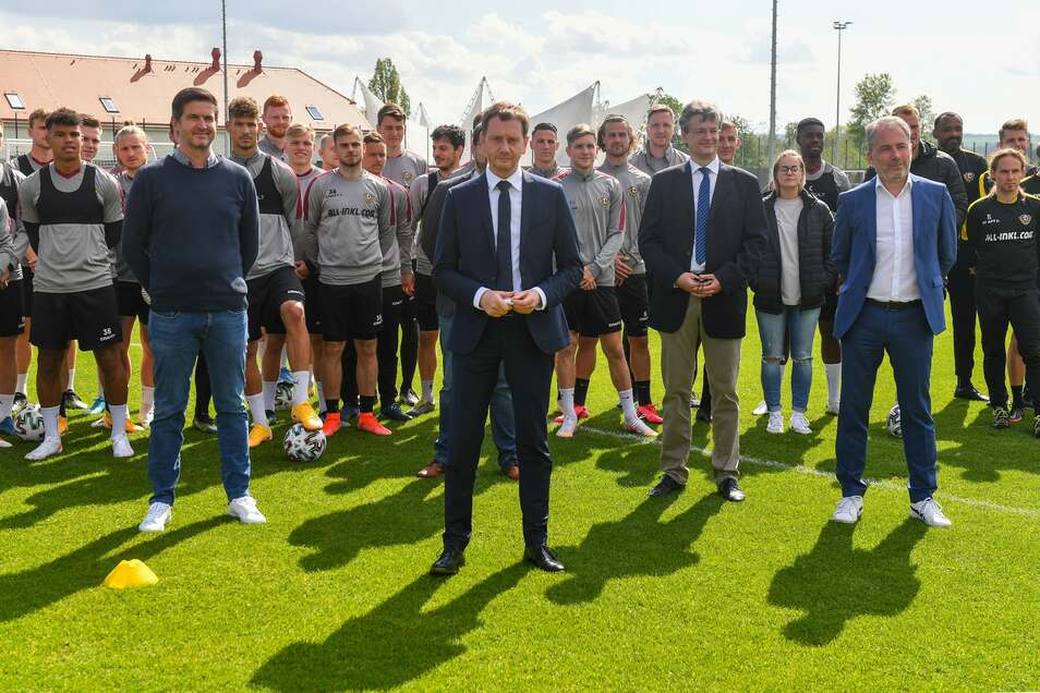 Gruppenbild mit MP, natürlich Corona-konform auf Abstand. Vor der Mannschaft haben sich Sportchef Ralf Becker (links), Michael Kretschmer und Dynamos kaufmännischer Geschäftsführer Jürgen Wehlend (rechts) aufgestellt.