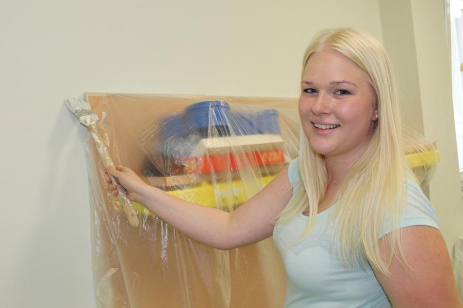 Erzieherin Anne Werner streicht eine Wand im Garderobenraum des Hortes.