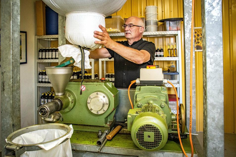 Dieter Horlacher bedient die Ölmühle. Von den Silos, die sich auf dem Boden befinden, fallen die Körner nach der Reinigung in den Sack. Danach werden sie ganz langsam gemahlen.