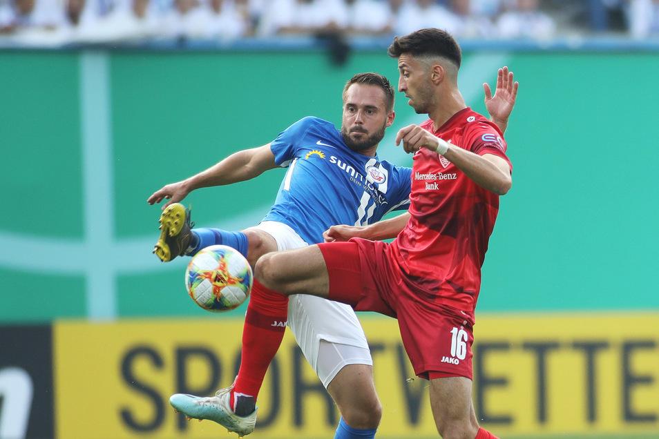 Hansa Rostocks Pascal Breier (links) kämpft mit Atakan Karazor vom VfB Stuttgart um den Ball.