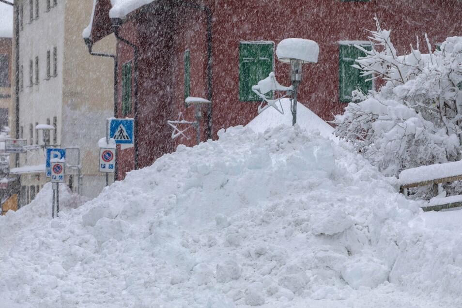 Schnee liegt hoch aufgetürmt am Straßenrand in der italienischen Gemeinde Brenner.