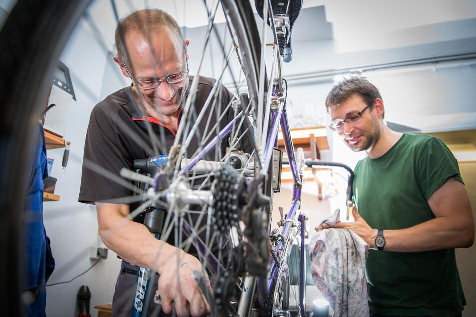"""Tobias Drößler (rechts) hat in der Selbsthilfewerkstatt """"Radskeller"""" viel gelernt. Jens Nitsche gibt Tipps und macht klare Ansagen, doch anpacken müssen die Kunden hier trotzdem selbst."""