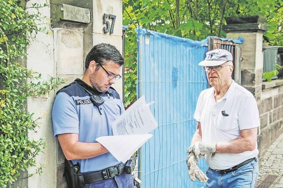 Ein Polizist prüft den von der Stadt verhängten Bescheid, der Eigentümer Dieter K. (r.) am weiteren Abriss hindern soll.