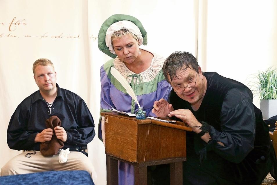Mit Erwerb des Stadtrechtes 1623 kommt es zu Konflikten zwischen Bauern und Handwerken. Bei einer Verhandlung versucht der Gerichtsschreiber (Oli Karo, rechts), die Situation zu klären. So behauptet die Böttchermeisterin (Astrid Dühring, Mitte), dass d