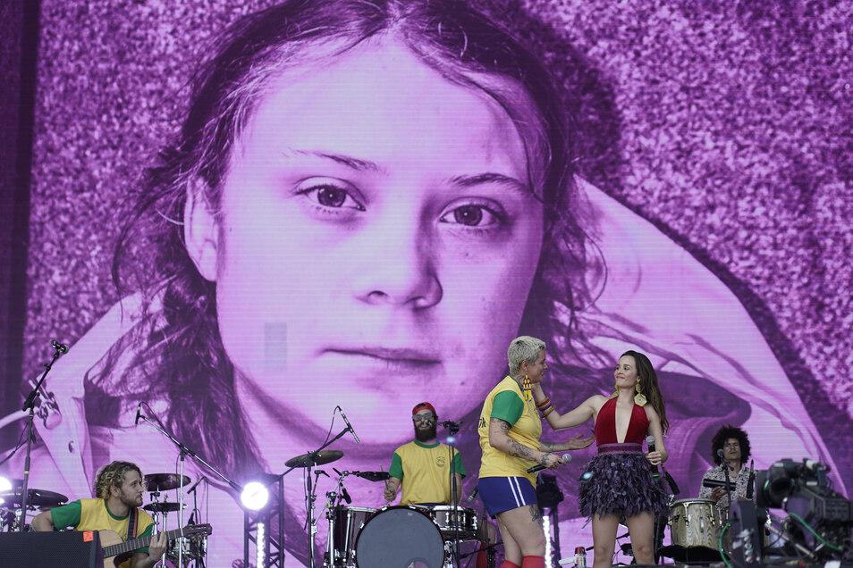 Ein Bild der schwedischen Umweltaktivistin Greta Thunberg wird bei dem Auftritt von brasilianischen und kolumbianischen Bands wie Monsieur Perine (l) bei Rock in Rio De Janeiro auf eine Großleinwand ausgestrahlt.