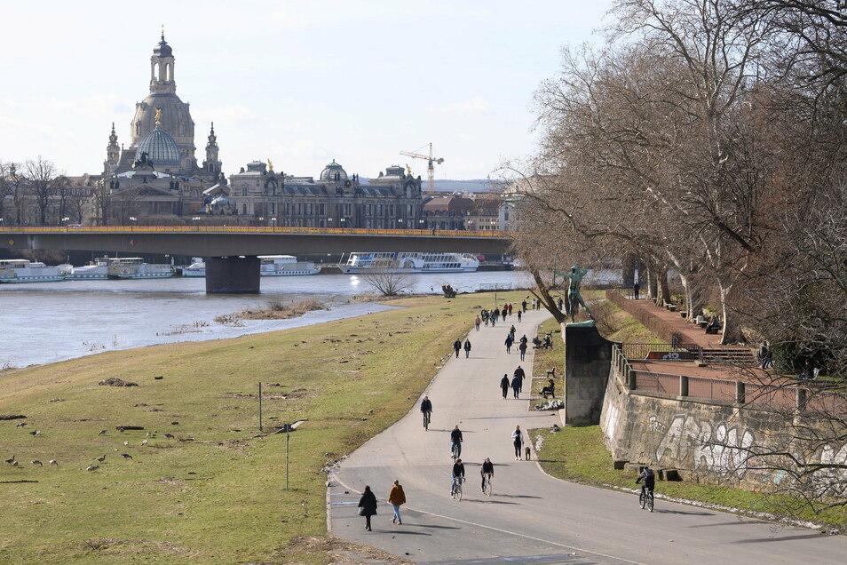 Passanten flanieren am Ufer der Elbe vor der Kulisse der Altstadt mit der Frauenkirche entlang.