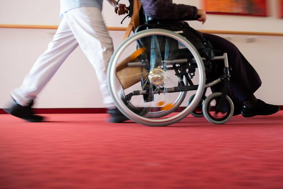 Ein Pfleger eines Pflegeheims schiebt eine Bewohnerin mit einem Rollstuhl. Im Landkreis Meißen spitzt sich die Lage in den Heimen wieder zu. In Coswig und Nossen kam zu erneuten Corona-Ausbrüchen.
