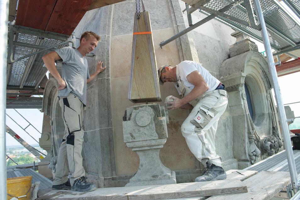 Max Witschel und Gerd Taubenheim setzen die Sandsteinobelisken auf und befestigen sie.