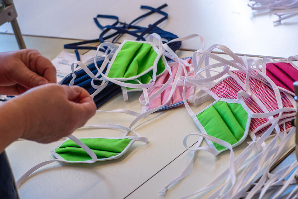 Eine Mitarbeiterin einer Textilforma sortiert gerade genähten Mundschutzmasken.