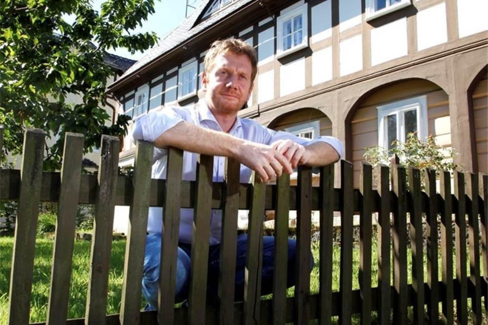 Ministerpräsident Michael Kretschmer im Garten seines Umgebindehauses in Waltersdorf.