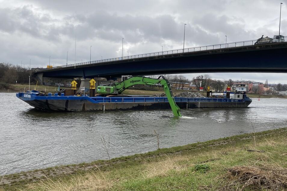 Unterhalb der Flügelwegbrücke in Dresden arbeitet dieser Bagger auf dem Schiff. Mit Gestein wird der Flussgrund über dem Abwassertunnel gesichert.