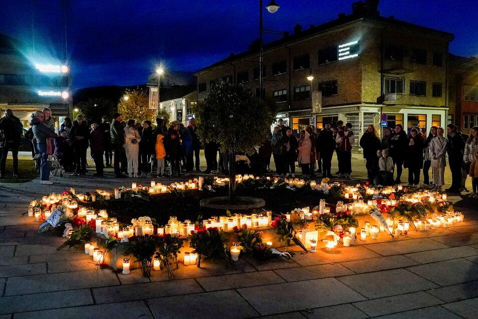 Personen stehen in Kongsberg vor Blumen und Kerzen, die in Gedenken an die Opfer niedergelegt wurden.