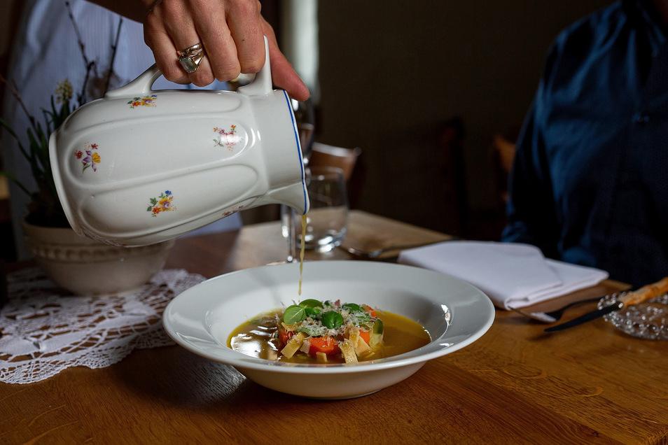 Geht wegen Corona so nicht mehr: Nachdem die Einlage der Gemüsesuppe aufgetragen ist, wird der Fond aus einer Omakaffeekanne extra zugegossen.