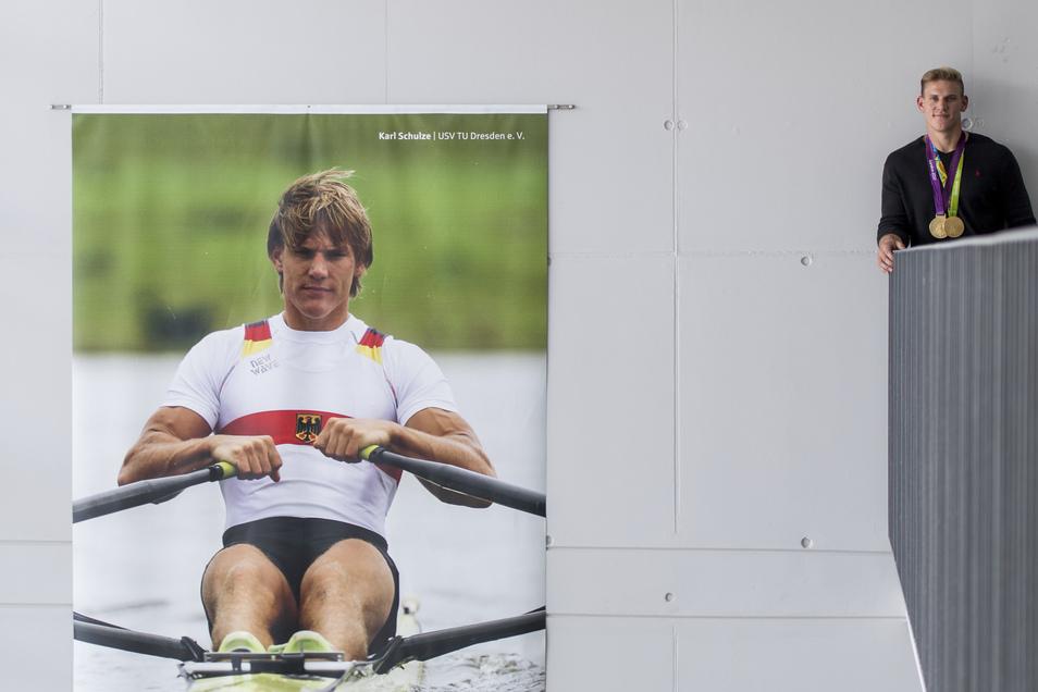 Karl Schulze neben seinem Poster im Treppenhaus der Sportschule.