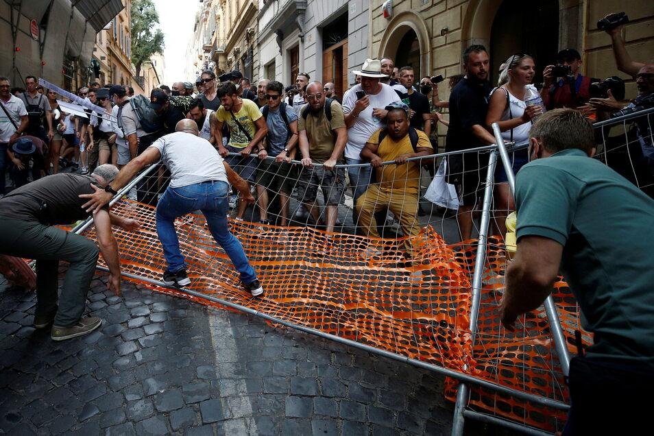 Rom: Demonstranten reißen einen Zaun auf der Via dei Due Macelli nieder. In Italien haben Gegner des sogenannten Grünen Passes gegen strengere Zutrittsregeln zu Restaurants und Bars als Reaktion auf die Corona-Pandemie protestiert.