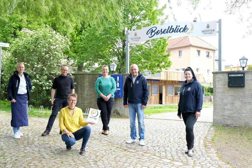 Tourismusexpertin Janine Häser (hockend) und der sächsische ADFC-Geschäftsführer Konrad Krause (2.v.l.) übergaben dem Team vom Boselblick in Sörnewitz das Bett+Bike Zertifikat.