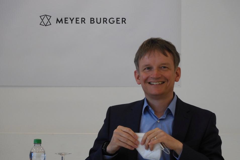 Geschäftsführer Gunter Erfurt vor dem neuen Logo von Meyer-Burger in Freiberg.