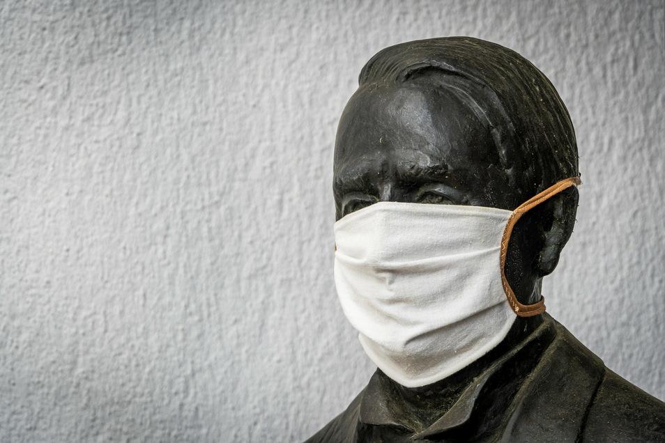 """Seit einem knappen Jahr gehört der Mund-Nasen-Schutz wegen der Corona-Pandemie inzwischen zum Alltag. Das Foto vom Juni 2020 zeigt die """"maskierte"""" Statue von Ehrenbürger Johann Christian Eberle vorm Nossener Rathaus."""
