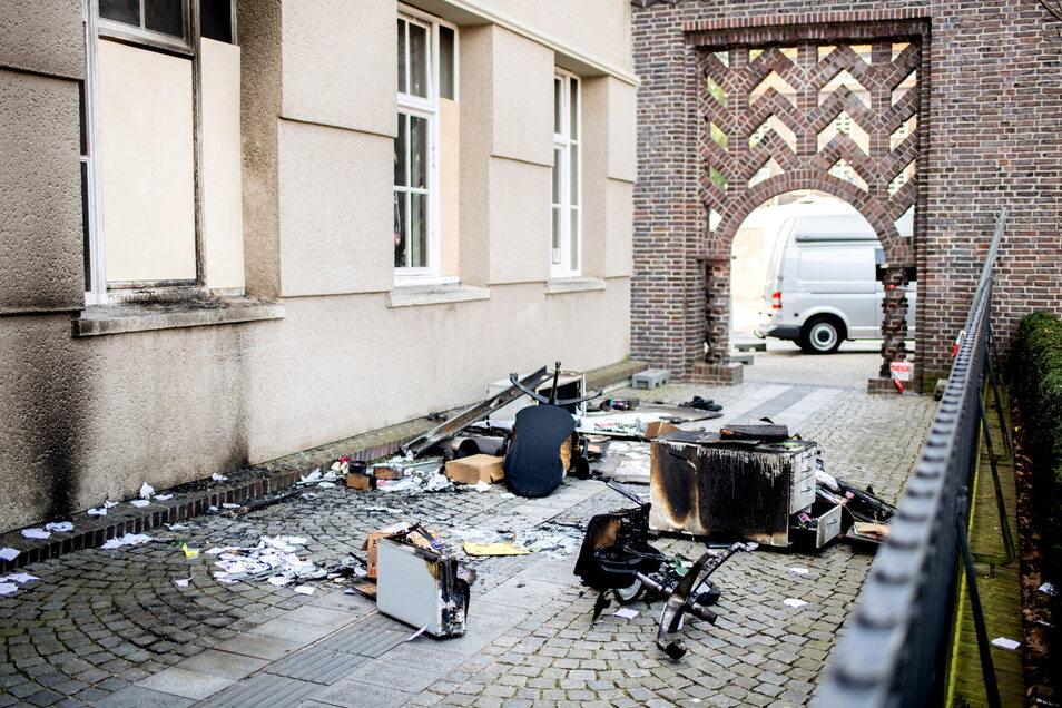 Verkohlte Möbelstücke liegen auf einem Gehweg vor dem Rathaus in Delmenhorst.