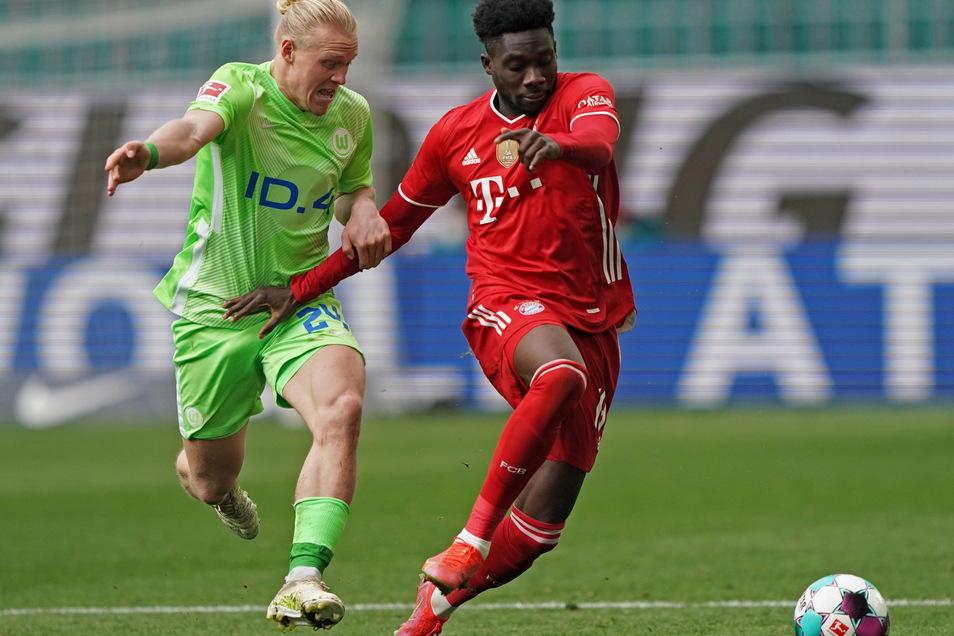 Wolfsburgs Mittelfeldspieler Xaver Schlager im Duell mit Münchens Abwehrspieler Alphonso Davies.